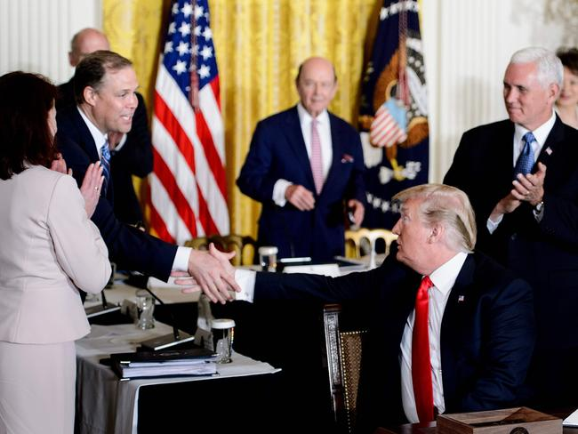 Donald Trump shakes the hand of NASA Administrator Jim Bridenstine after signing a directive about space during at the White House. Picture: AFP
