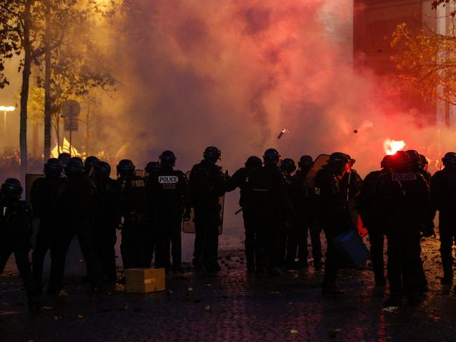 Riot police stand amidst smoke, as they face demonstrators during a protest of Yellow vests (Gilets jaunes) against rising oil prices and living costs, near the Arc of Triomphe. Picture: AFP