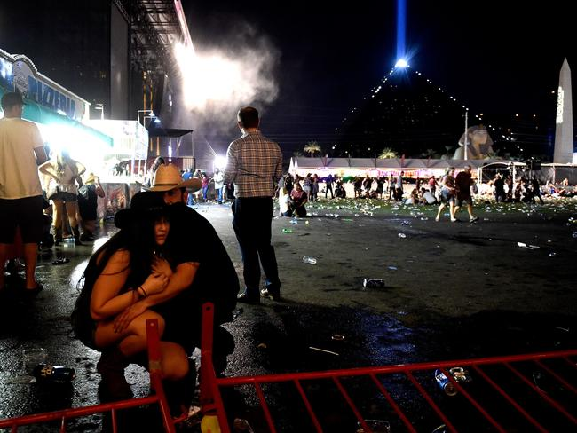 People take cover at the Route 91 Harvest country music festival after gunfire was heard on Sunday night. Picture: David Becker/Getty Images.