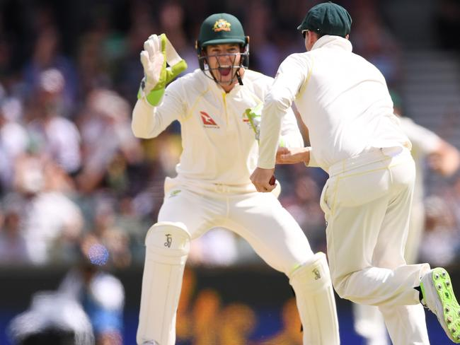 Tim Paine celebrates the wicket of Joe Root with captain Steve Smith.