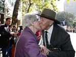 """25/4/16 Win Cartan (90) kisses her husband Arthur """"Doug"""" Carton (95) as he stops past her during the 100th ANZAC Day March celebrations in Sydney which was held for the first time on Elizabeth St in the Sydney CBD. Arthur """"Doug"""" Cartan fought in New Guinea with the 2nd 1st battalion infantry as a corporal. This is the second year he has taken an impromptu detour to kiss his wife after marching every year. Picture: Adam Yip"""
