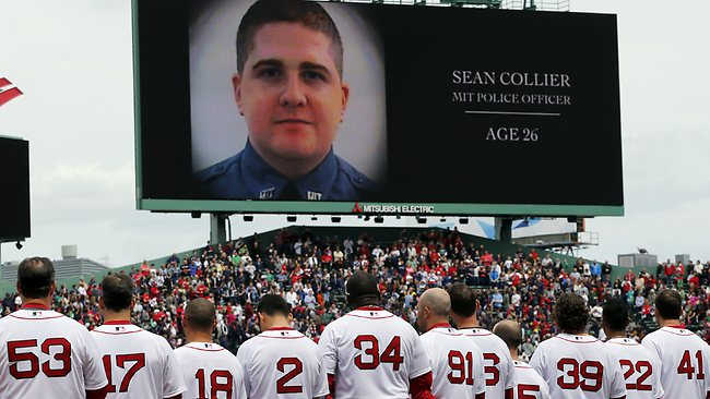 The Boston Red Sox line up during a tribute to victims of the Boston Marathon bombing and its aftermath, as an image of Massachusetts Institute of Technology Police Officer Sean Collier is displayed on the scoreboard.