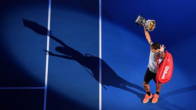 Federer poses with the trophy.