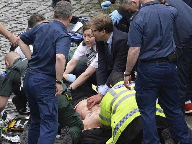Conservative Member of Parliament Tobias Ellwood, centre, helps emergency services attend to an injured person outside the Houses of Parliament, London, Wednesday, March 22, 2017. Picture: Stefan Rousseau/PA via AP
