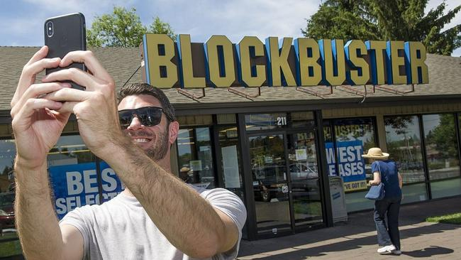 A visitor takes a selfie in front of the last Blockbuster video store, located in Bend, Oregon. Picture: Ryan Brennecke/The Bulletin/Associated Press