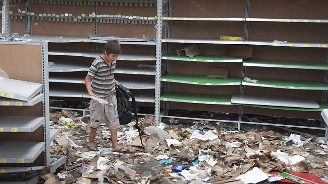 A child walks through debris in a looted supermarket in San Miguel de Tucuman. Picture: AP Photo/Bruno Cerimele