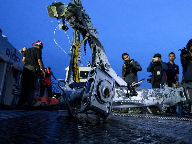 Members of the search team lift part of the landing gear of the ill-fated Lion Air flight JT 610 during search operations at sea off the coast from Karawang. Picture: AFP