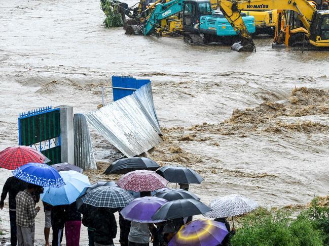 Nepali residents look at rising floodwaters. Picture: PRAKASH MATHEMA / AFP