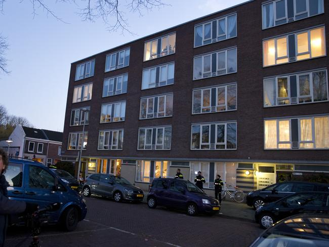 People look at the apartment, bottom right illuminated window, where the suspect was arrested in Utrecht, Netherlands. Picture: AP