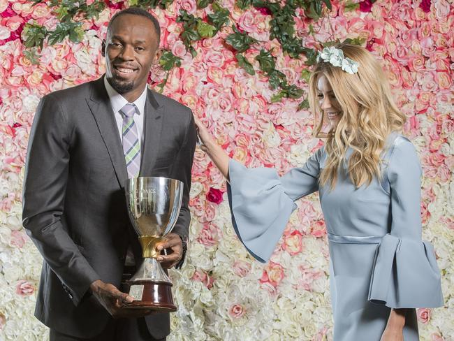 Usain Bolt with Jennifer Hawkins at Crown holding the Crown Oaks Cup. Picture: Jason Edwards