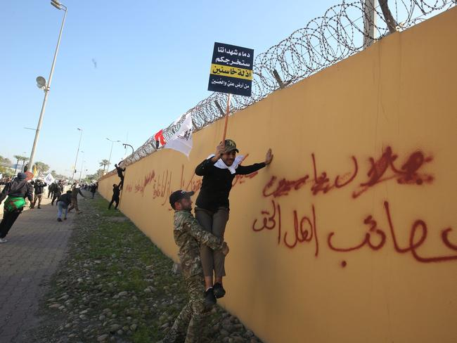 A member of an Iraqi Shiite paramilitary group helps a fellow protesters holding a placard denouncing the United States climb on the outer wall of the US embassy in Baghdad's Green Zone during an angry demonstration. Picture: AFP