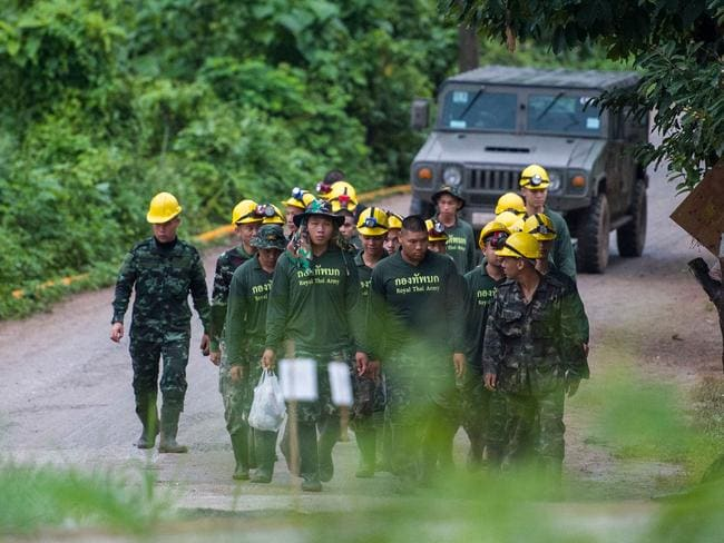 Thai soldiers walk out from the Tham Luang cave area as operations continue. Picture: AFP