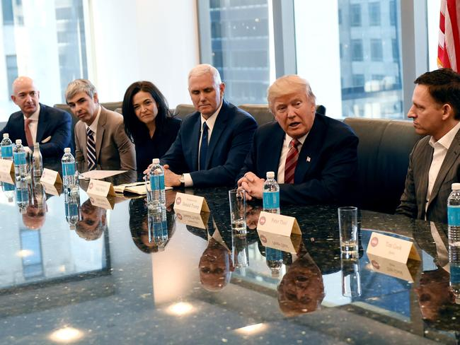 Amazon's chief Jeff Bezos, Larry Page of Alphabet, Facebook COO Sheryl Sandberg, Vice President Mike Pence and Donald Trump pictured with Peter Thiel. Picture: AFP/TIMOTHY A. CLARY
