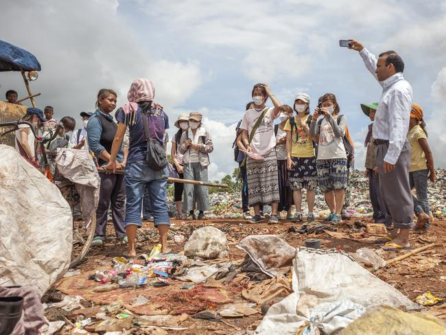 A woman who is working in the landfill demonstrates the use of the hook to tourists. Picture: David Rengel / AnHua
