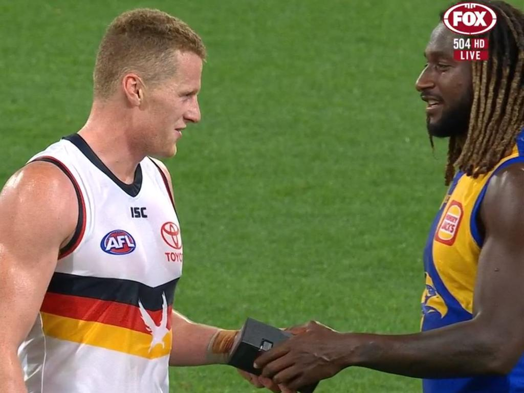 Nic Naitanui hands Reilly O'Brien a new phone after West Coast's game against Adelaide.