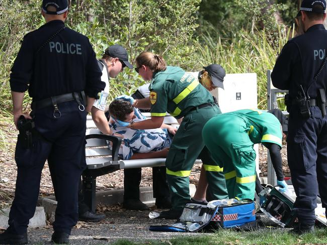 Paramedics help the passed-out man. He was eventually revived and taken away by paramedics.