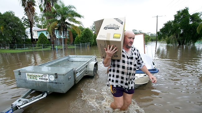 Friends and neighbours help evacuate belongings from houses in Keogh St, West Ipswich. Picture: Mark Calleja