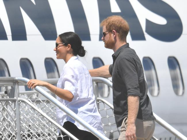 Britain's Prince Harry said they fly commercial where possible. Pictured, the Duke of Sussex and his wife Meghan boarding a plane in Australia. Picture: AAP/Darren England