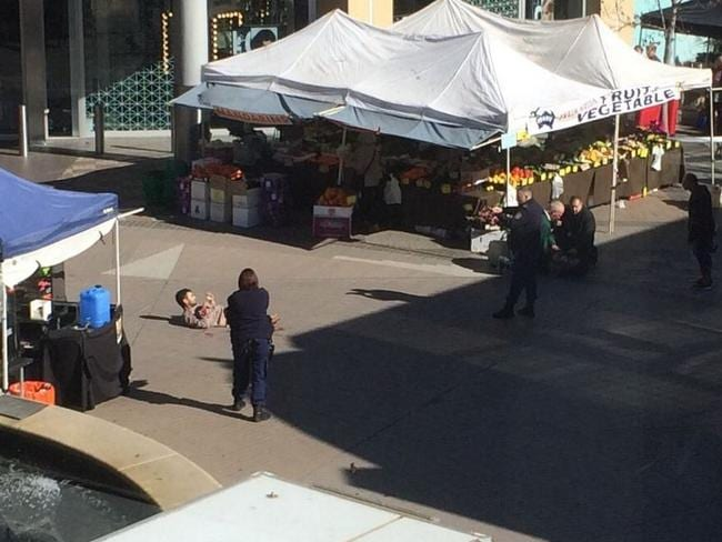 "The knifeman lies on the ground ""30 seconds after the gunshot"". Picture: David Henry"