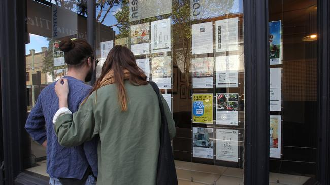 A couple look through the window of a real estate agency in Surry Hills, NSW. The RBA board noted housing turnover was starting to rise.