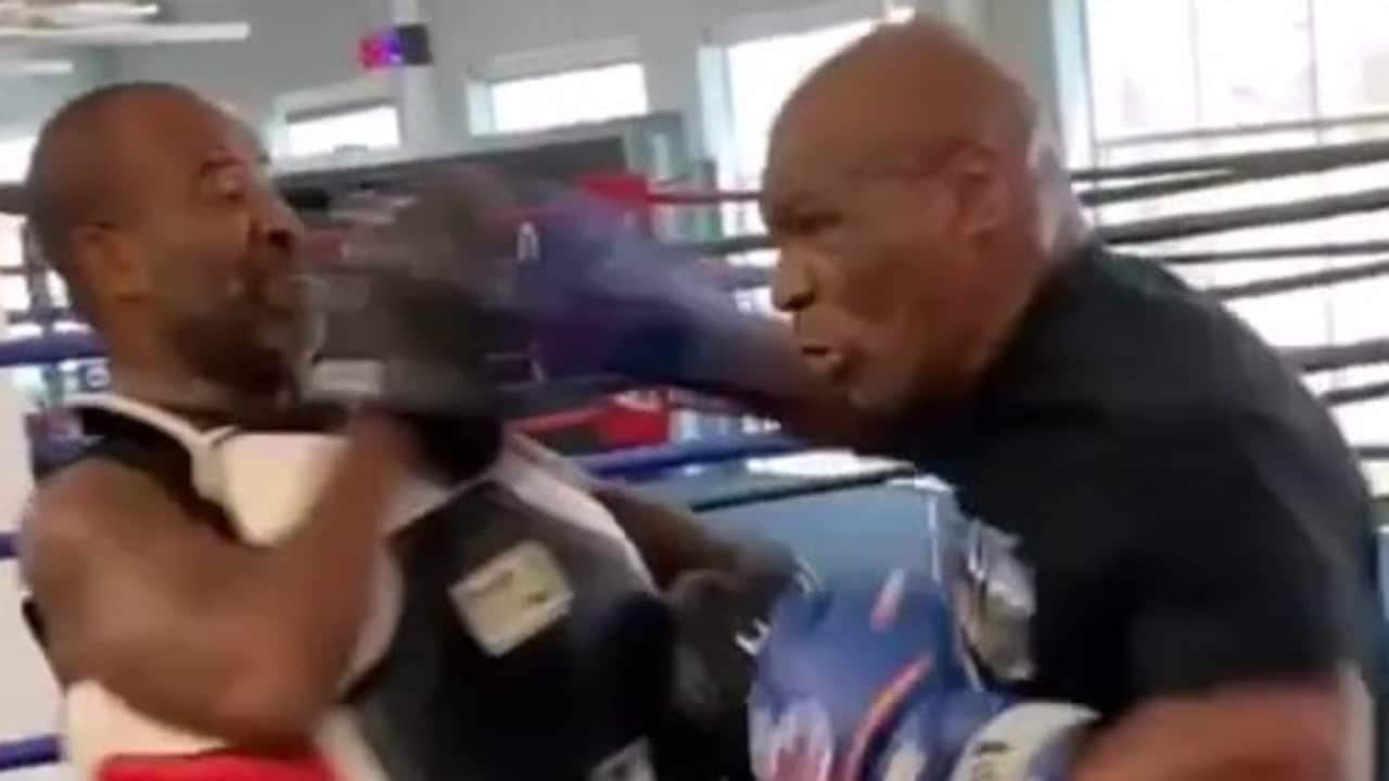 Mike Tyson almost takes his trainer's head off.