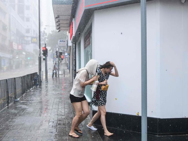 Residents walk through the rain during Super Typhoon Mangkhut in Hong Kong yesterday. Picture: Anthony Wallace
