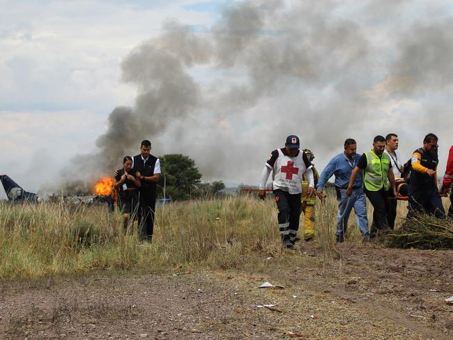 Red Cross workers and rescue workers carry an injured person as shocked flight crew walk away from the burning plane.