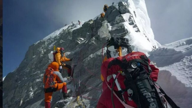 Mountaineers push up past the Hillary Step on the way to the summit of Everest.