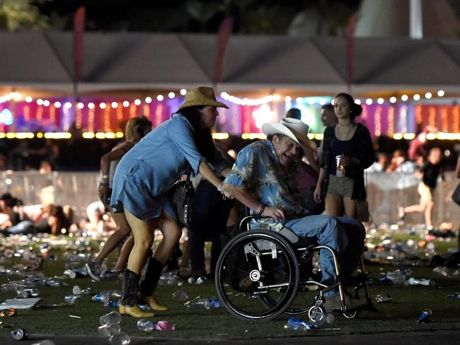 A man in a wheelchair is taken away from the Route 91 Harvest country music festival after the shooting began.
