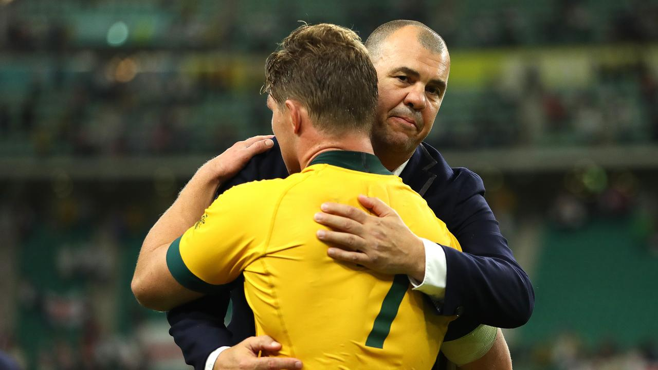Michael Cheik embraces Michael Hooper following their QF loss to England at Oita Stadium.