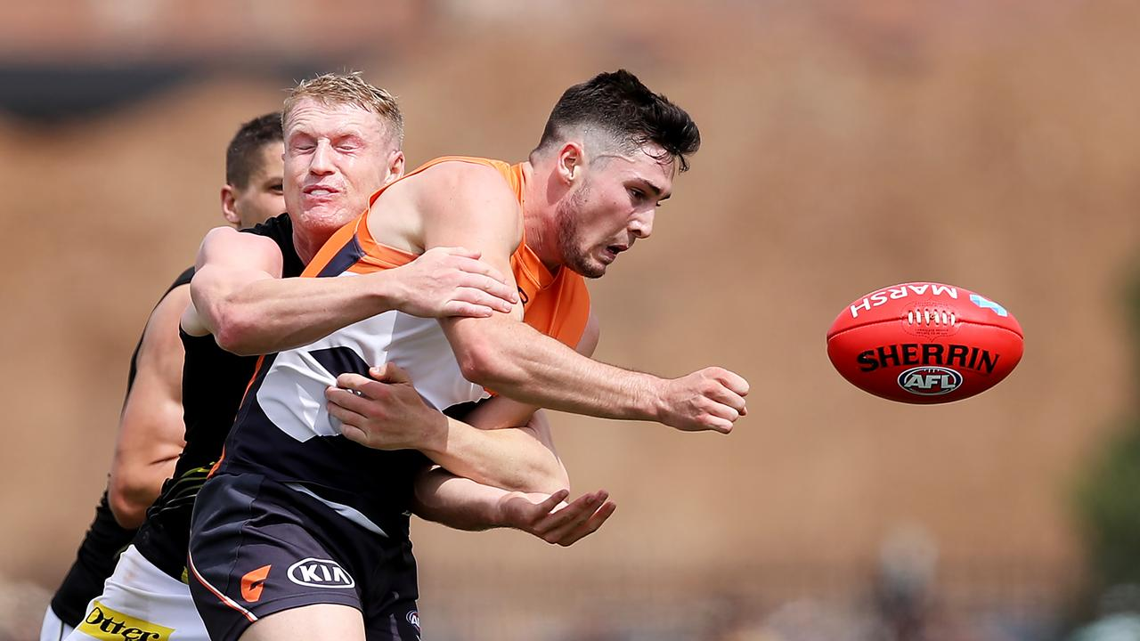 Lachlan Ash is tackled by Josh Caddy in the Marsh Community Series.