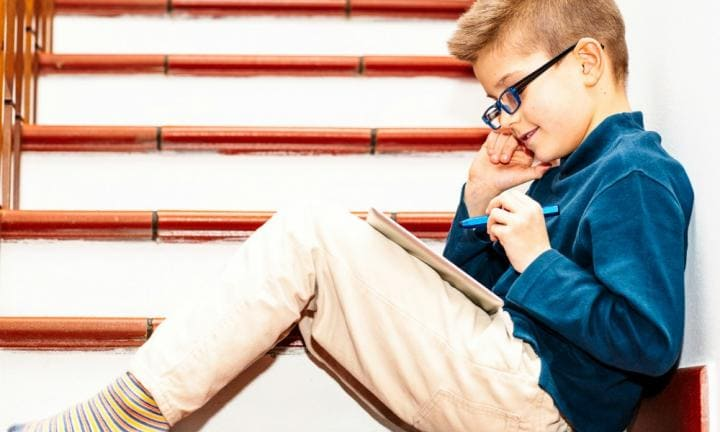 Boy seven years old sitting on staircase home and drawing on touchpad.