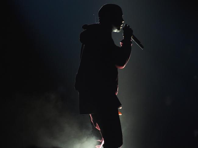 Working the trackie ... Kanye West on stage. Picture: John Shearer/Invision/AP