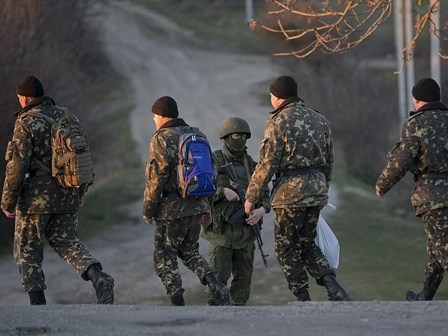 Sent packing ... Ukrainian soldiers walk by a pro-Russian soldier in Perevalne, Ukraine, after being evicted from their base in Crimea. Picture: Vadim Ghirda