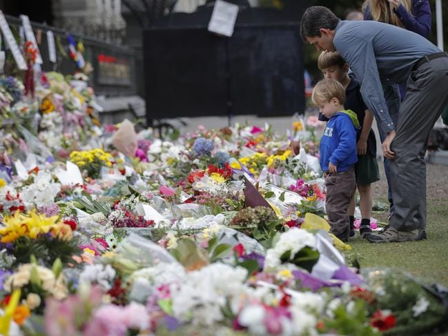 Mourners lay flowers on a wall at the Botanical Gardens in Christchurch, New Zealand. Picture: AP