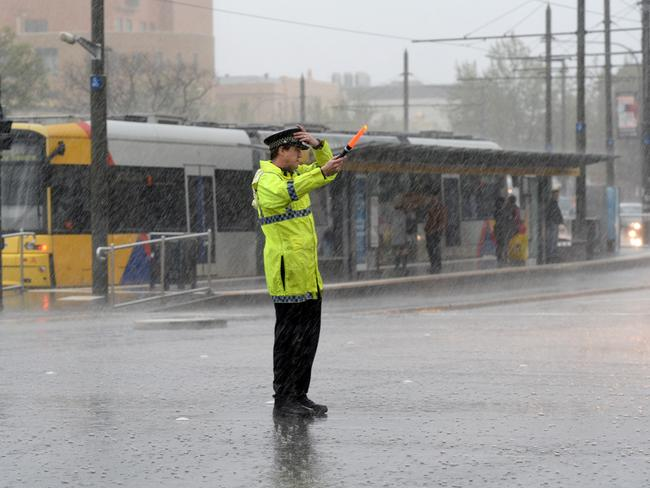 Police directing traffic due to a blackout during stormy weather in Adelaide. Picture: Greg Higgs