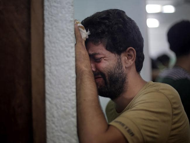 No shelter ... a Palestinian man breaks down after the death of a relative following an Israeli strike at a UN school in Jebaliya refugee camp. Picture: Khalil Hamra