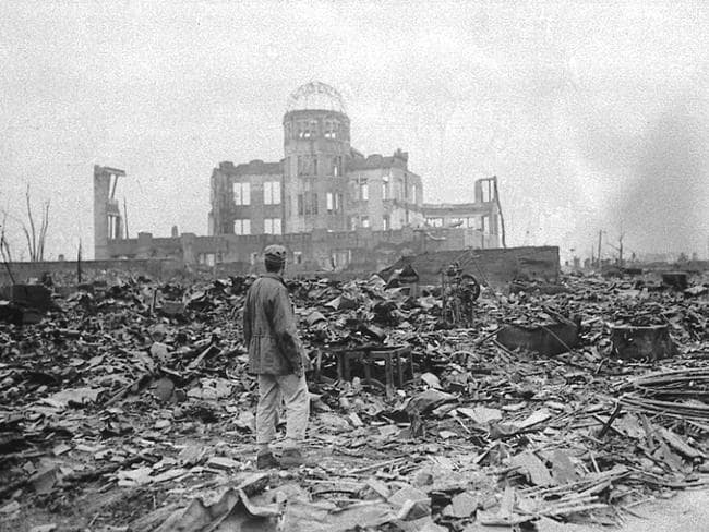 An allied correspondent stands in a sea of rubble before the shell of a building that once was a movie theatre in Hiroshima on September 8, 45.