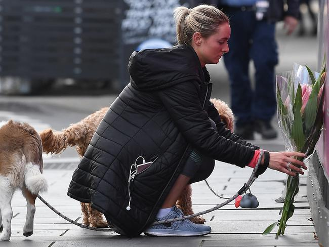 A woman places a floral tribute Chapel Street, South Yarra in Melbourne. Picture: Julian Smith/AAP