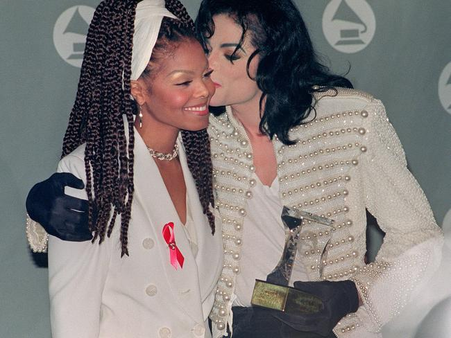 Michael Jackson kisses his sister Janet Jackson (L) after she presented him with the Grammy Legend Award at the 35th Annual Grammy Awards February 24,1993. Picture: AFP