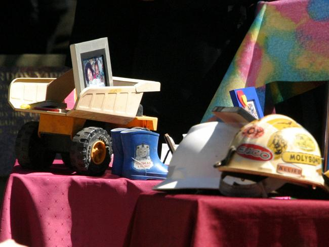 Bas and Malee's tractor and galoshes and Peter Poulson's RFS helmet on their coffins at the funeral. Picture: Scott Hornby.