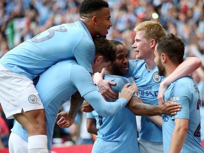 Raheem Sterling of Manchester City celebrates with teammates Bernardo Silva and Kevin De Bruyne.