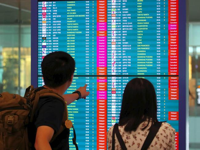 Passengers look at an information board displaying cancelled flights as Typhoon Lingling hits the Korean peninsula. Picture: AFP