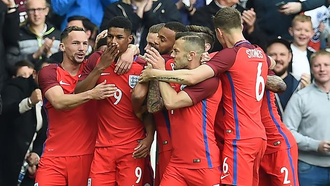 England's striker Marcus Rashford (2nd L) celebrates after scoring.