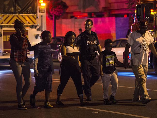 Police escort civilians away from the scene of a shooting in Toronto. Picture: AP