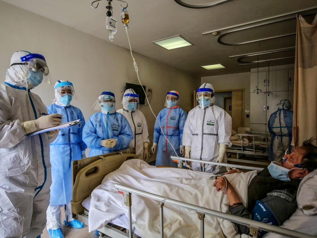 Medical personnel speak to a patient infected with the COVID-19 coronavirus at the Wuhan Red Cross Hospital in the Chinese province of Hubei. Image: AFP