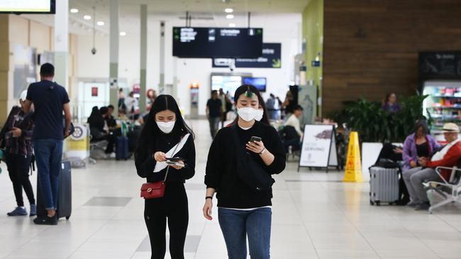 Tourists wearing masks at Gold Coast Airport as the Coronavirus epidemic continue sto spread. Picture Glenn Hampson