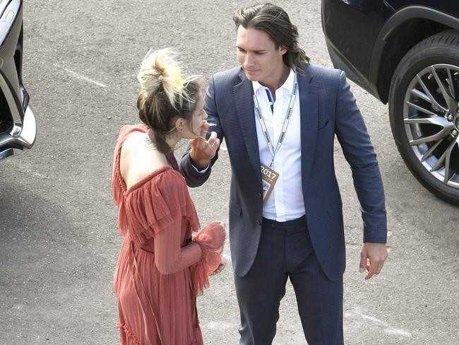 Tyler Green helps Paris Jackson with a cigarette at the Melbourne Cup. Picture: Splash