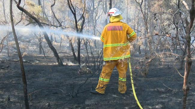 Damping down scorched earth and bush at Cattai Ridge Rd, Maraylya. Picture: TNV