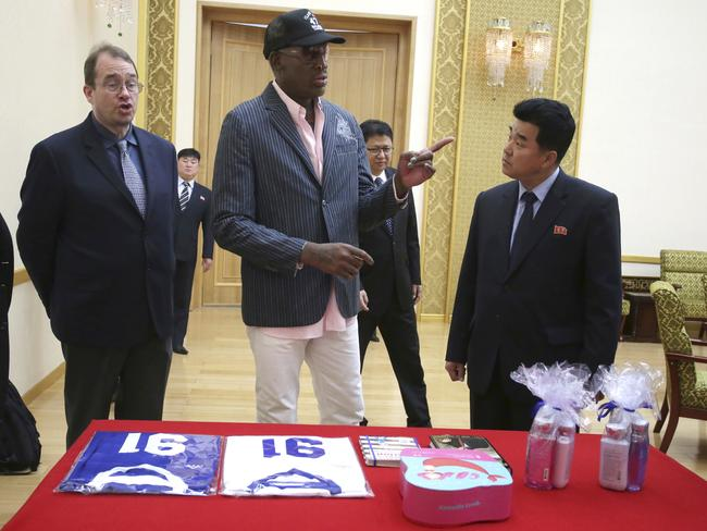 "Dennis Rodman presents gifts, including autographed basketball jerseys, bath soaps and books ""Where's Waldo?"" and ""The Art of the Deal"", to North Korea's Sports Minister Kim Il-guk. Picture: AP Photo/Kim Kwang Hyon"